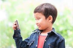 el muchacho toma el selfie con el teléfono móvil Imagen de archivo