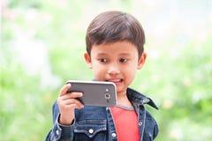 el muchacho toma el selfie con el teléfono móvil Imagenes de archivo
