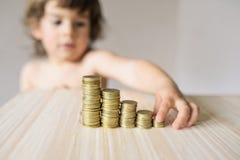 El muchacho toma la moneda Fotos de archivo libres de regalías