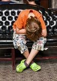 El muchacho toma un resto en un sofá Fotos de archivo