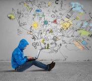 El muchacho trabaja con el ordenador portátil Foto de archivo