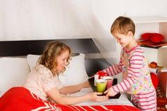 El muchacho trajo el desayuno a la madre en una cama Fotografía de archivo