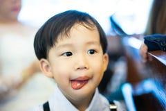 El muchacho travieso come secretamente el caramelo, él está jugando en la iglesia con fotografía de archivo