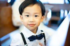 El muchacho travieso come secretamente el caramelo, él está jugando en la iglesia con imagen de archivo
