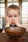 El muchacho travieso rubio lindo rechaza comer Imagenes de archivo