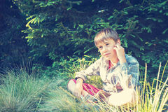 El muchacho triste en auriculares se sienta y sueña en la hierba enorme Foto de archivo libre de regalías