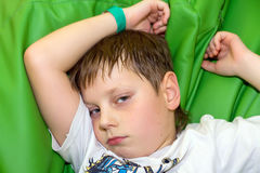 El muchacho triste en un sofá verde lo dañó Fotografía de archivo libre de regalías