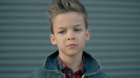 El muchacho triste es de pensamiento y de mirada de la cámara Cara de un pequeño muchacho triste serio que es Retrato del primer almacen de metraje de vídeo