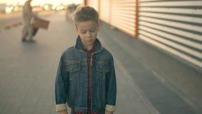 El muchacho triste está caminando abajo de la calle y del pensamiento Cara de un pequeño muchacho triste serio que es Retrato almacen de video