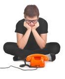 El muchacho triste está esperando el phonecall previsto foto de archivo