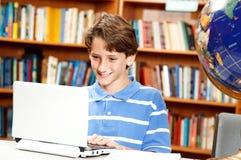 El muchacho utiliza el ordenador en escuela Imagen de archivo libre de regalías