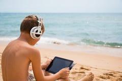 El muchacho utiliza un Tablet PC que se sienta en una playa Foto de archivo