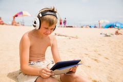 El muchacho utiliza un Tablet PC que se sienta en una playa Imagen de archivo libre de regalías