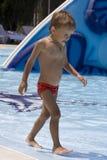El muchacho va en el borde de la piscina Foto de archivo libre de regalías