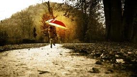 El muchacho va a saltar a través del parque con un paraguas del shinig almacen de metraje de vídeo