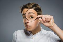 El muchacho ve a través la lupa, ojo del niño que mira con la lente de la lupa sobre gris fotos de archivo
