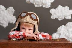 El muchacho vestido como piloto del aeroplano se sienta entre las nubes con la maleta vieja y los sueños imagen de archivo libre de regalías