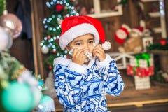 El muchacho vestido como Santa Claus, intenta encendido una barba blanca Foto de archivo