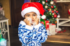 El muchacho vestido como Santa Claus, intenta encendido una barba blanca Imagen de archivo libre de regalías