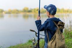El muchacho viaja con una mochila en la orilla del río Fotografía de archivo