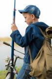 El muchacho viaja con una mochila en la orilla del río Foto de archivo