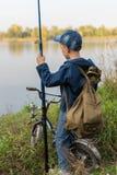 El muchacho viaja con una mochila en la orilla del río Imagen de archivo