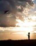 El muchacho vuela la cometa. Foto de archivo libre de regalías