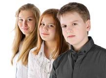 El muchacho y dos muchachas permanecen en línea Foto de archivo
