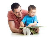 El muchacho y el padre del niño leyeron un libro Imagen de archivo