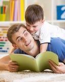 El muchacho y el padre del niño leyeron un libro en piso en casa Foto de archivo