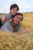 El muchacho y el padre en el heno Fotografía de archivo libre de regalías