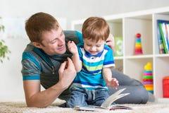 El muchacho y el papá del niño leyeron un libro en piso en casa Fotografía de archivo libre de regalías
