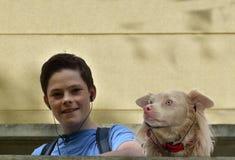 El muchacho y el perro escuchan música Fotografía de archivo libre de regalías