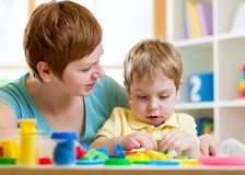 El muchacho y la madre del niño que juegan la arcilla colorida juegan Imágenes de archivo libres de regalías