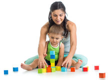 El muchacho y la madre del niño juegan así como los juguetes del bloque Fotografía de archivo
