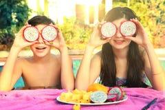 El muchacho y la muchacha adolescentes con la fruta del dragón circundan Fotografía de archivo libre de regalías