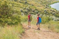 El muchacho y la muchacha adolescentes con las mochilas en la parte posterior van en un alza, viaje, paisaje hermoso Imagenes de archivo
