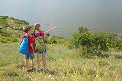 El muchacho y la muchacha adolescentes con las mochilas en la parte posterior van en un alza, viaje, paisaje hermoso Imagen de archivo libre de regalías