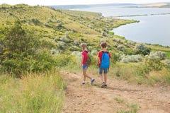 El muchacho y la muchacha adolescentes con las mochilas en la parte posterior van en un alza, viaje, paisaje hermoso Fotografía de archivo libre de regalías