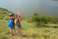 El muchacho y la muchacha adolescentes con las mochilas en la parte posterior van en un alza, viaje, paisaje hermoso Fotografía de archivo