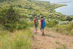 El muchacho y la muchacha adolescentes con las mochilas en la parte posterior van en un alza, viaje, paisaje hermoso Fotos de archivo