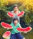 El muchacho y la muchacha adolescentes se divierten que come la sandía Foto de archivo libre de regalías