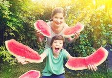 El muchacho y la muchacha adolescentes se divierten que come la sandía Fotografía de archivo libre de regalías
