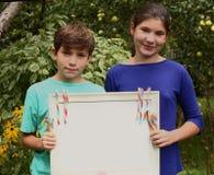 El muchacho y la muchacha adolescentes sostienen la hoja vacía del papel en blanco en marco con el caramelo Foto de archivo
