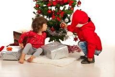 El muchacho y la muchacha arreglan el árbol de navidad Imagen de archivo