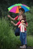El muchacho y la muchacha bajo el paraguas en parque rasgan la hierba Imagen de archivo libre de regalías