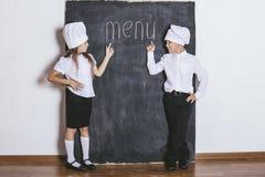 El muchacho y la muchacha cocina con el tablero de la pizarra bajo menú del texto fotografía de archivo libre de regalías