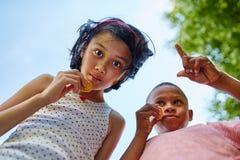 El muchacho y la muchacha comen las galletas imágenes de archivo libres de regalías