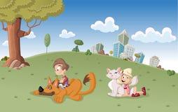 El muchacho y la muchacha con el perro y el gato en ciudad parquean Imagen de archivo libre de regalías