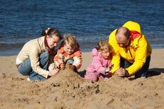 El muchacho y la muchacha con los padres juegan en arena en la playa Foto de archivo libre de regalías
